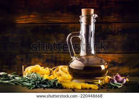 Olive oil the basic raw material of Mediterranean cuisine along with pasta garlic pepper and fresh thyme in an old wooden rustic still life. - stock photo