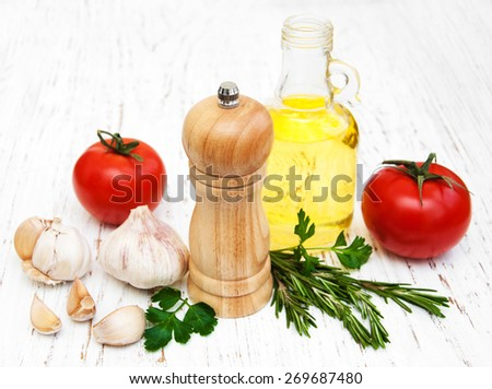 olive oil,   tomato and garlic on a old wooden background - stock photo