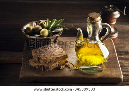 Olive oil with bread on a wooden table.