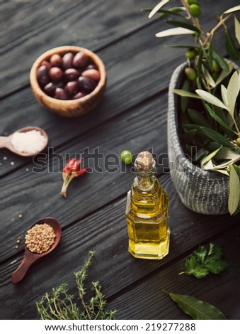 Olive oil with herbs. Mediterranean ingredients: rosemary, olives, thyme, sage, salt, oregano - stock photo
