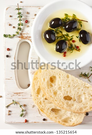 Olive oil with olives and spices. Delicious dip and fresh bread ciabatta. - stock photo