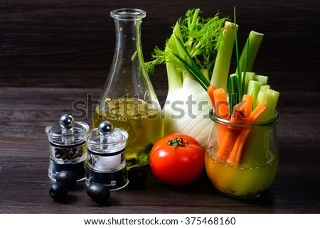 Olive oil with pepper mill tomato and vegetables on a dark background - stock photo
