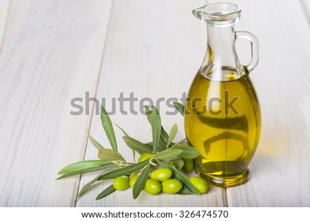 Olive oil with raw olives and its leaves - stock photo