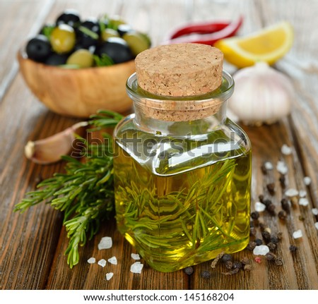 Olive oil with rosemary and spices on a brown table - stock photo