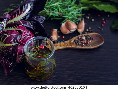 Olive oil with rosemary, garlic, chicory and pepper. Olive oil in bottle with rosemary and spices on a brown table. Olive oil flavored with spices and other ingredients. Selective focus. - stock photo