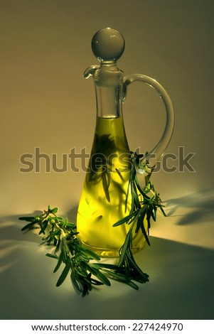 Olive oil with rosemary in a glass jug, on dark background - stock photo