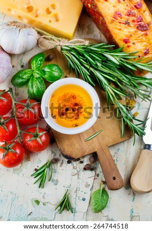 Olive oil with spices in a bowl and cherry tomatoes with herbs - stock photo