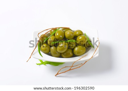 olive tapas decorated with leaves and twigs, served on the ceramic plate - stock photo