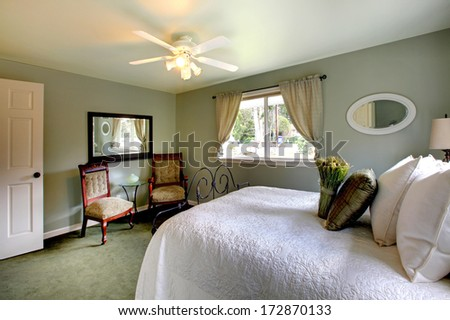 Olive tones bedroom with antique iron frame bed, green carpet and aristocratic chairs