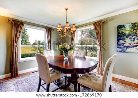 Olive tones dining room with old-fashioned dining table set, chandelier, curtains and carpet - stock photo