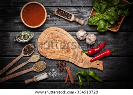 Olive wood board with different spices on wooden surface - stock photo