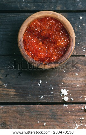 Olive wood bowl of red caviar over old wooden table. Top view - stock photo