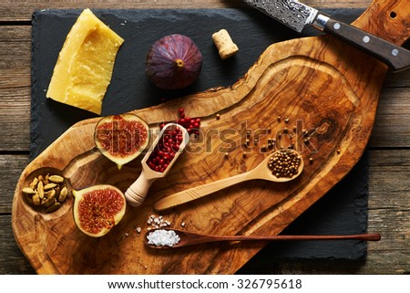Olive wood cutting board with spices and fig over slate - stock photo