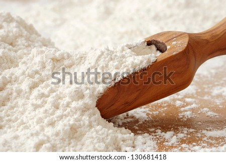 Olive wood measuring scoop with baking flour.  Macro with shallow dof. - stock photo