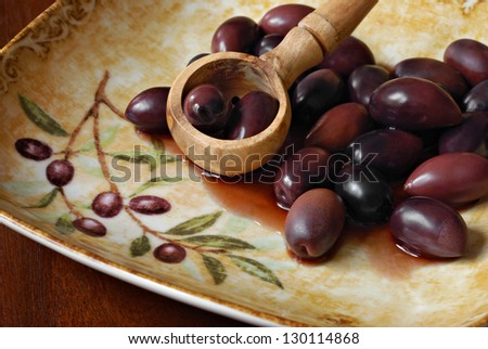 Olive wood slotted spoon with Kalamata olives on decorative plate with matching pattern.  Macro with shallow dof. - stock photo