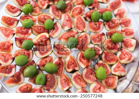 Olives and figs on dish - stock photo
