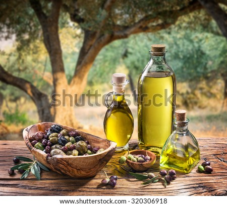 Olives and olive oil in a bottle on the background of the evening olive grove. - stock photo