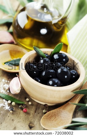 Olives and Olive Oil on an old tablel - stock photo