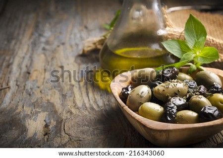 Olives and olive oil on rustic wooden table - stock photo