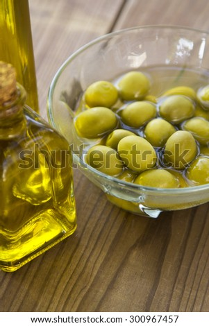 olives and olive oil on wooden background