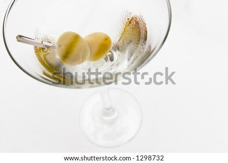 olives in martini glass with wet droplets on glass -  filled with freshly poured martini - stock photo