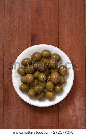 olives in white dish on brown background - stock photo