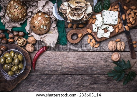 Olives, nuts and  sheep cheese with bread in rustic style - stock photo