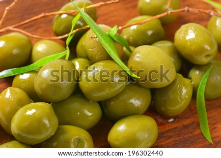 olives tapas, served on the wooden cutting board - stock photo