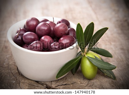 Olives with leaves on a wooden background. - stock photo