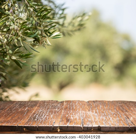 Olives with old wooden table. Blur nature background. - stock photo