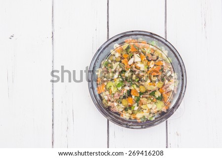 Olivier traditional salad in a black plastic container isolated on a white wooden background. - stock photo