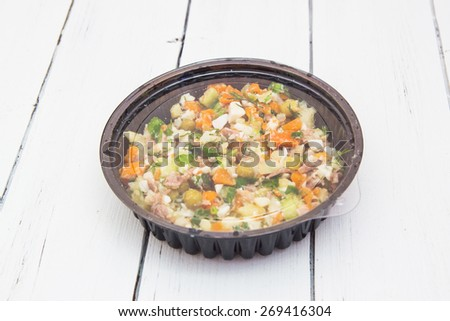 Olivier traditional salad in a black plastic container isolated on a white wooden background.
