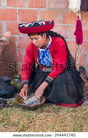 Ollantaytambo, Peru - circa June 2015: Woman in traditional Peruvian clothes uses natural dye for Alpaca and Llama wool near Cusco, Peru - stock photo