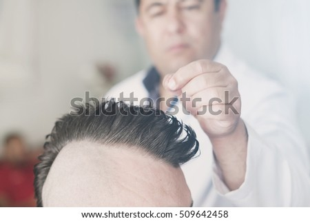 Oludeniz, Turkey, April 28, 2016: Barber makes a mohawk hairstyle at the adult man