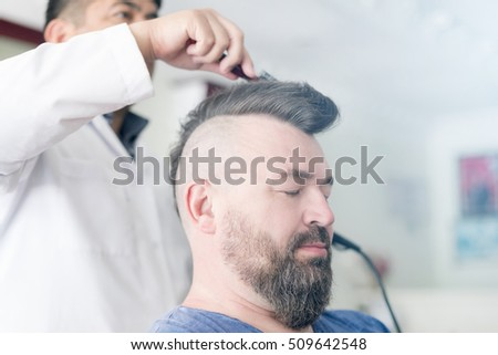Oludeniz, Turkey, April 28, 2016: Male barber makes hair styling using a hair dryer of a adult bearded man with a mohawk. Toned