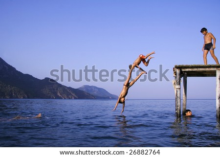 OLYMPOS, TURKEY -  AUGUST 3: Young local boys jump into sea from pier on August 3, 2007 in Olympos, Turkey. Olympos is located 90 km southwest of Antalya city near Kemer. - stock photo