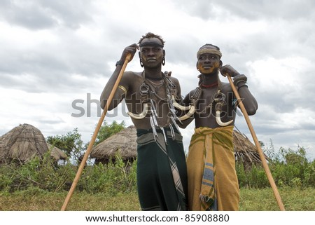 OMA VALLEY, ETHIOPIA - AUG 11: Mursi men posing in the village, the ethnic groups in the The Omo valley Could disappear Because of Gibe III hydroelectric dam on Aug 11, 2011 in Omo Valley, Ethiopia. - stock photo