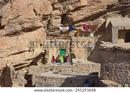 Omani women relaxing outside a traditional stone house in a small cliff hamlet near Sroot in the Jebel Akhdar mountains of the Sultanate of Oman. - stock photo