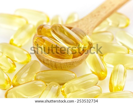 Omega-3 capsules in wooden spoon - stock photo