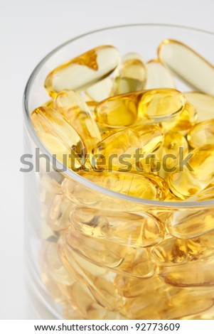 Omega 3 fish oil capsules in glass cup of full health - stock photo