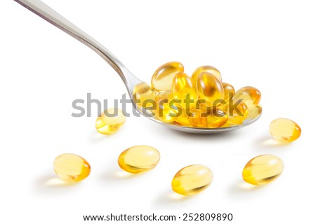 Omega-3 pills on spoon. ,  file includes a excellent clipping path - stock photo