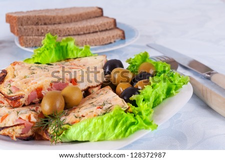 Omelet slices on lettuce leaves with brown bread