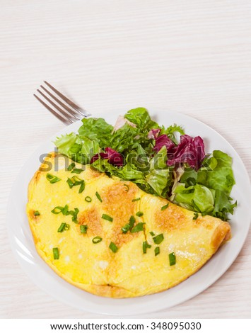 omelet with fresh mixed salad leaves - stock photo