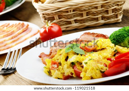 Omelet with fried bacon on the white plate