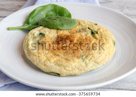 Omelet with spinach on plate - stock photo