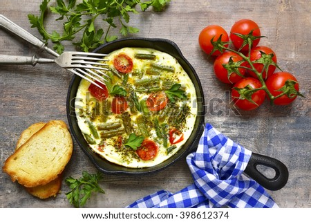 Omelet with tomatoes and asparagus bean in a skillet pan. - stock photo