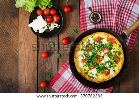 Omelet with tomatoes, parsley and feta cheese in pan. Top view