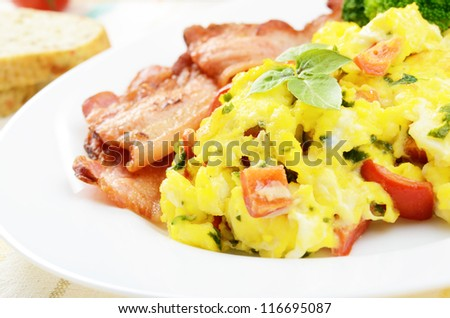 Omelet with vegetables, fried bacon and bread
