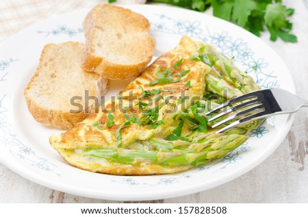 omelette with asparagus, greens and toast on the plate horizontal close-up