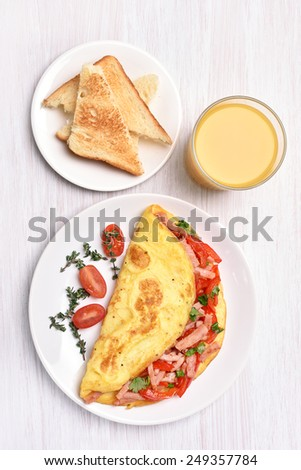 Omelette with vegetables and ham, top view - stock photo